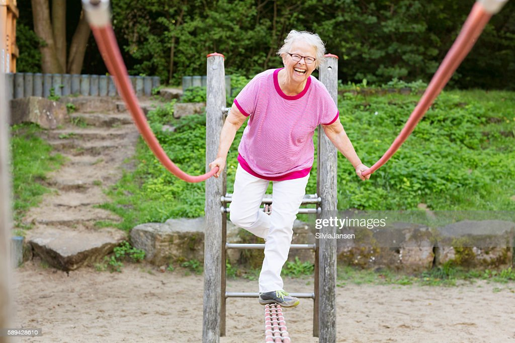 cheerful senior woman on playground balancing