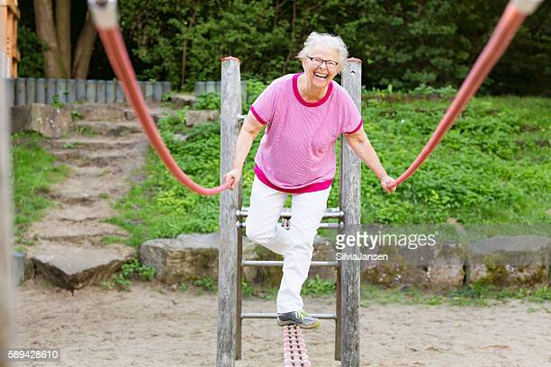 cheerful  senior woman on playground balancing - fat old lady stock photos and pictures