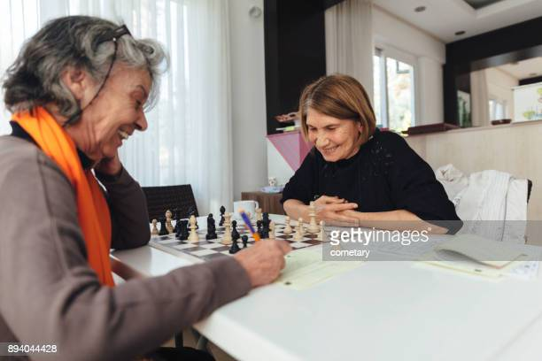 cheerful senior woman playing chess - roommate stock pictures, royalty-free photos & images