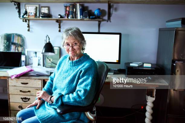 cheerful senior woman sitting at desk and smiling towards camera - looking at camera stock pictures, royalty-free photos & images