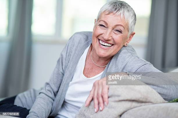 Cheerful senior woman sitting on a couch