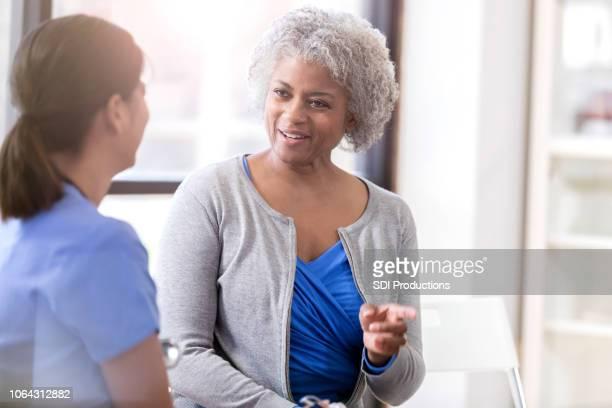 cheerful senior woman talks with physician - questão da mulher imagens e fotografias de stock