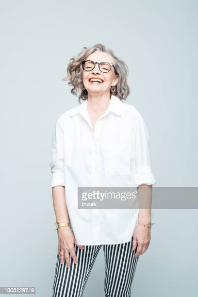 cheerful senior woman wearing shirt and striped trousers - izusek stock pictures, royalty-free photos & images