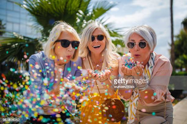 cheerful senior women celebrating by blowing confetti in the city - festeggiamento foto e immagini stock