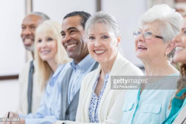 Senior femenino alegre goza de seminario de educación continua