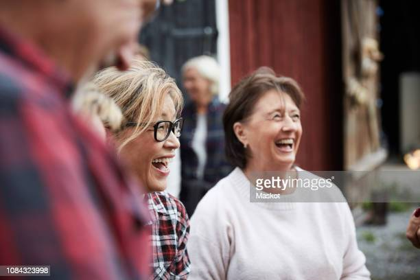 cheerful senior women looking away while standing at farm during party - mixed farming stock pictures, royalty-free photos & images