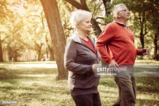 Cheerful seniors couple exercising in park.