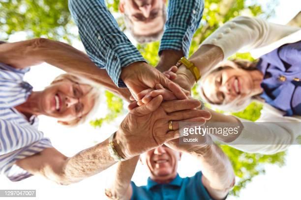 fröhliche senioren stapeln hände - izusek stock-fotos und bilder