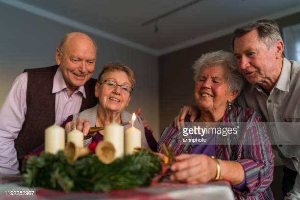 fröhliche senioren am ersten advent zu hause - monat stock-fotos und bilder