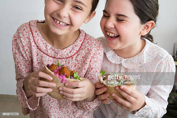 Cheerful Siblings Eating Falafel Wrap Sandwich At Home