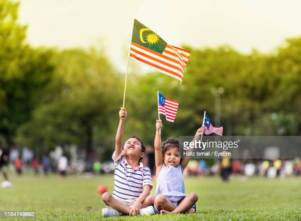 cheerful siblings holding malaysian flags - malaysian culture stock pictures, royalty-free photos & images