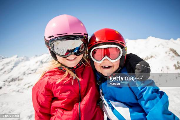 cheerful siblings in ski-wear standing against snowcapped mountain - 6 7 anni foto e immagini stock