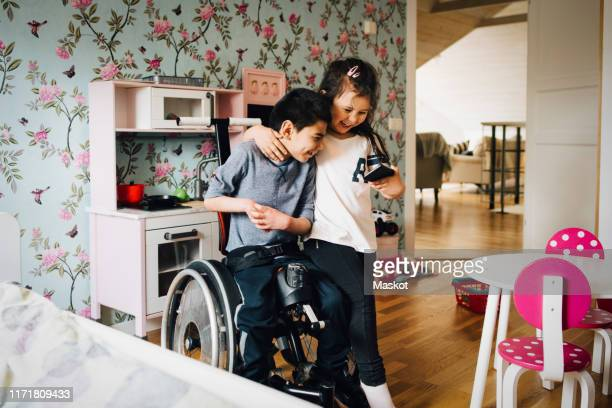 cheerful sister watching video with autistic brother on mobile phone at home - pessoas com deficiência imagens e fotografias de stock