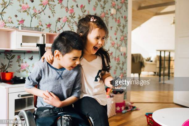 cheerful sister watching video with autistic brother on smart phone at home - differing abilities fotografías e imágenes de stock