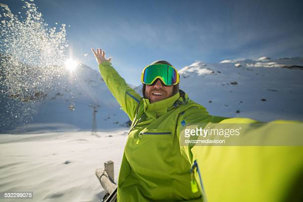 Cheerful skier taking selfie on ski slopes throwing snow-Sunset time