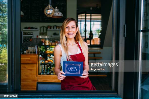 a cheerful small business owner with open sign - small stock pictures, royalty-free photos & images