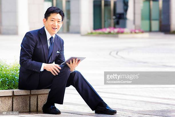 Cheerful smiling Japanese job hunter portrait outdoors with tablet
