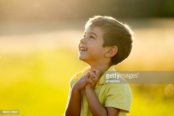 cheerful smiling little boy outdoors in summer sunlight upper body - suplicar imagens e fotografias de stock