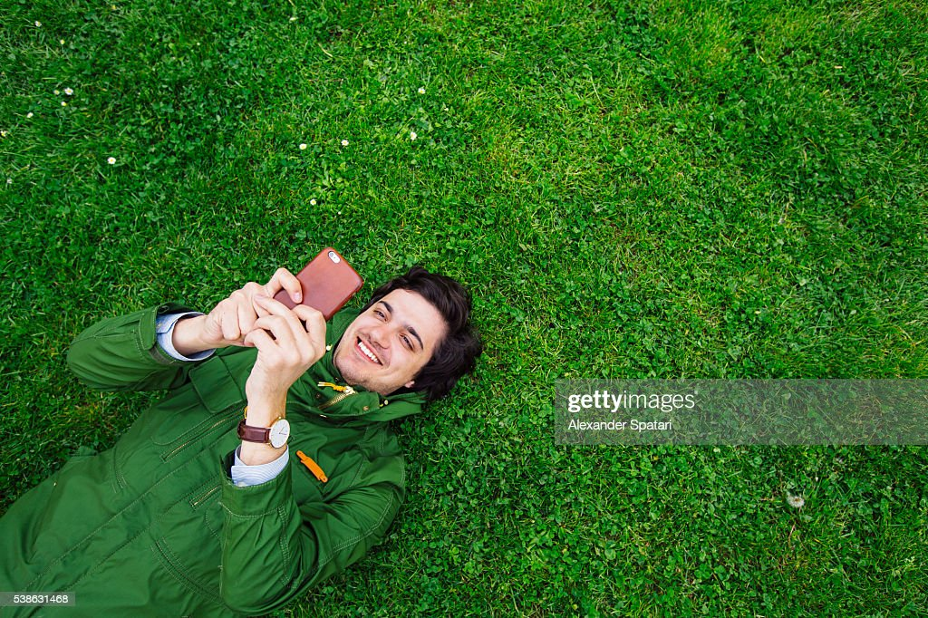 Cheerful smiling young man lying on grass with smartphone : Stock Photo