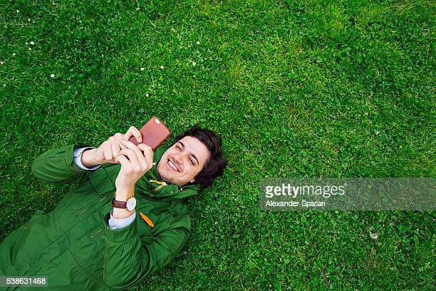 Cheerful smiling young man lying on grass with smartphone
