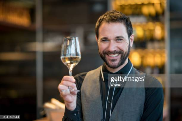 Cheerful sommelier tasting wine and looking at camera smiling