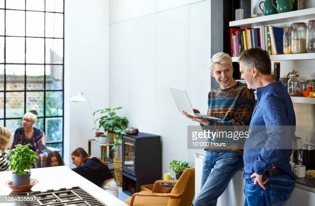 cheerful son with laptop talking to father in kitchen - parenting stock pictures, royalty-free photos & images