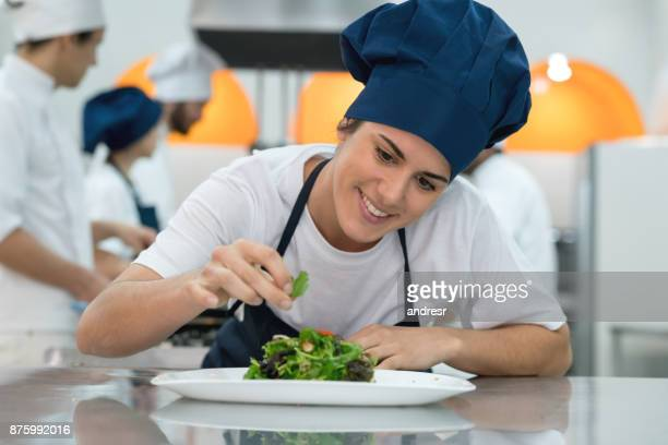 cheerful sous chef adding details to a salad looking very happy and smiling - food and drink stock pictures, royalty-free photos & images