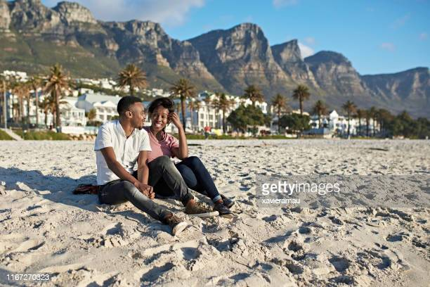 cheerful south african couple enjoying camps bay beach - província do cabo ocidental imagens e fotografias de stock