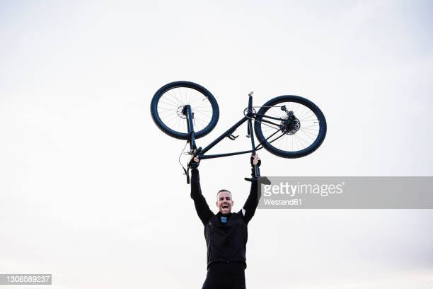 cheerful sportsman lifting bicycle against sky - picking up stock pictures, royalty-free photos & images