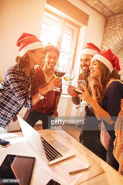 Cheerful start up team toasting to upcoming New Year.