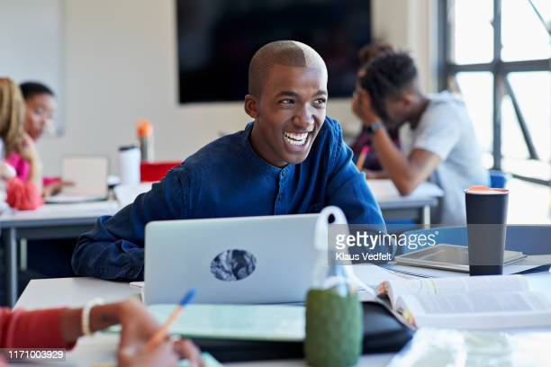 cheerful student looking away with laptop at desk - africa stock pictures, royalty-free photos & images