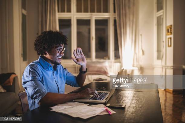 cheerful student talking over a laptop computer with his friends - video conference stock pictures, royalty-free photos & images