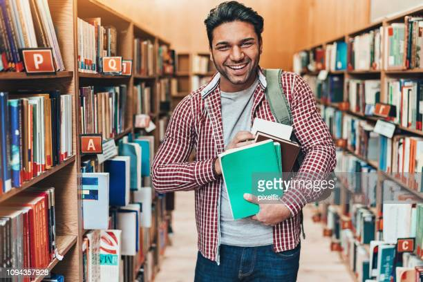 cheerful student with bunch of books - man holding book stock pictures, royalty-free photos & images