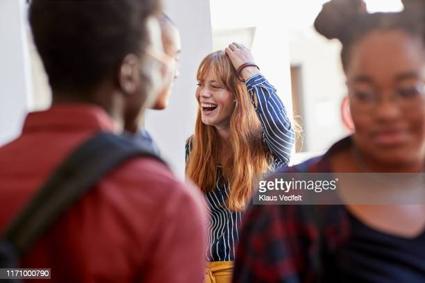 cheerful student with hand in hair amidst friends - hairstyle stock pictures, royalty-free photos & images