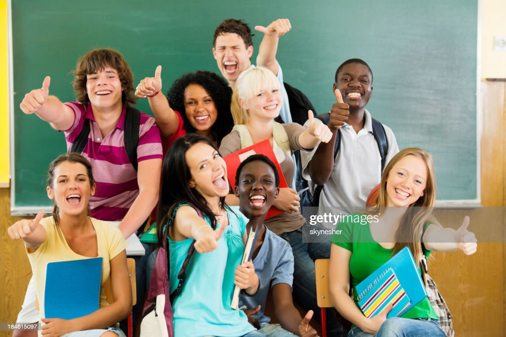 Cheerful students looking at the camera with their thumbs up. : Stock Photo