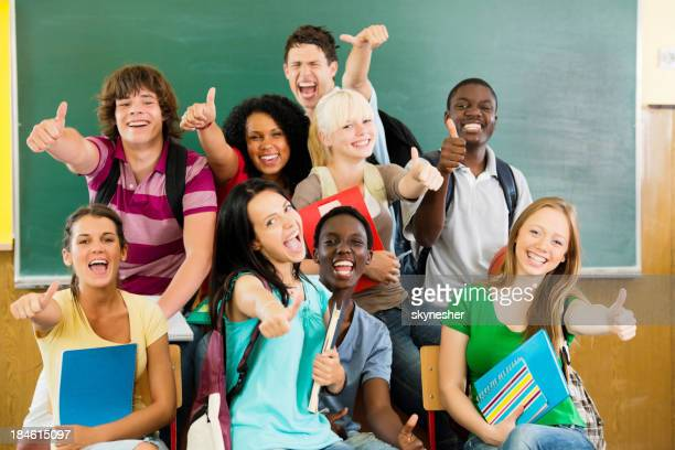 Cheerful students looking at the camera with their thumbs up.