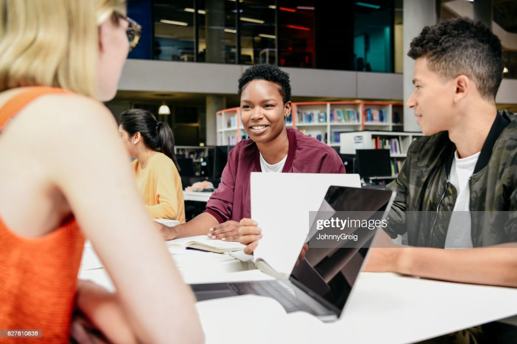 Cheerful students sitting in library using laptops and talking : Stock Photo