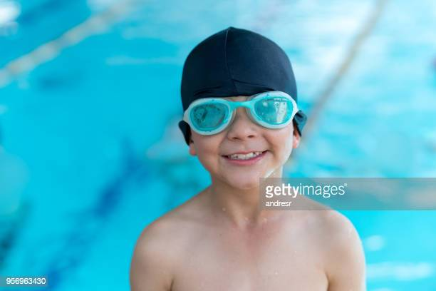 Cheerful sweet boy at the swimming pool wearing his goggles and swimming cap looking at camera very happy