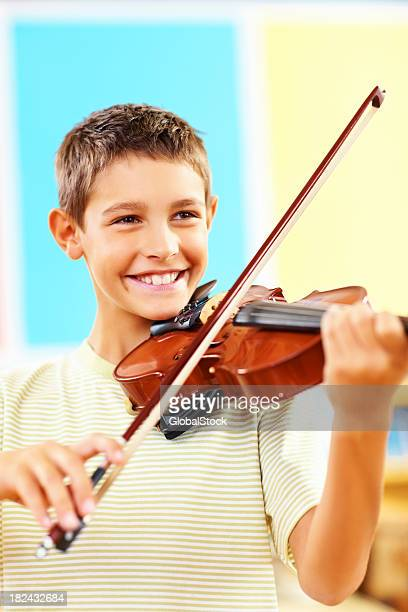 Cheerful talented young school boy playing the violin