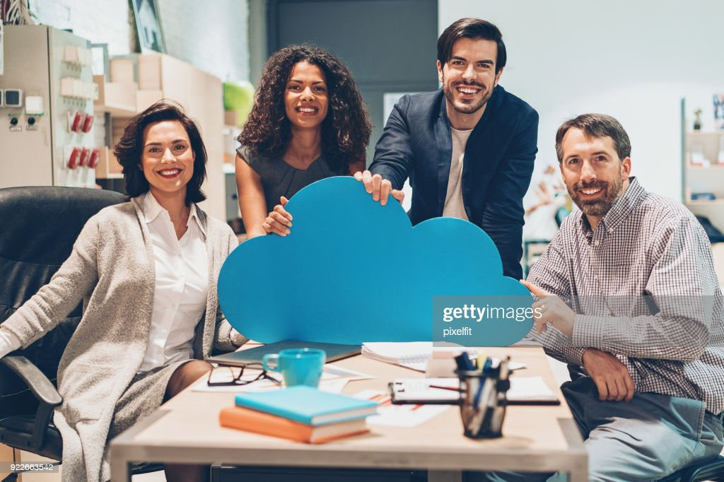 Cheerful team of professionals holding a big blue cloud : Stock Photo