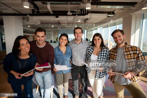 cheerful team of young people at the office all smiling at camera very happy - hispanolistic stock photos and pictures