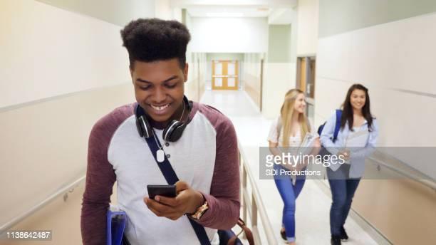gai adolescent garçon bénéficie de téléphone intelligent entre les classes - crossbody bag photos et images de collection