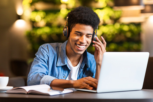 Cheerful teen guy with headset looking at laptop 1172141143