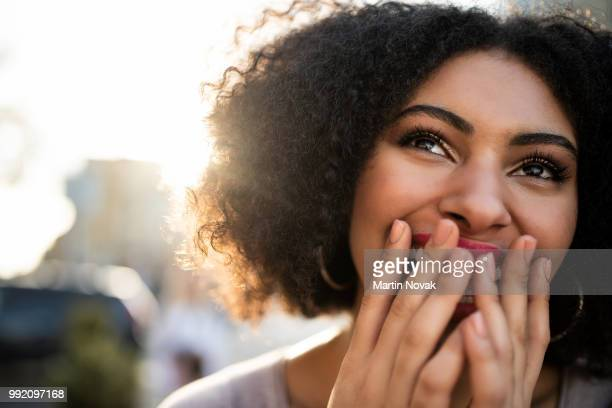 cheerful teen woman covering her mouth - überraschung stock-fotos und bilder