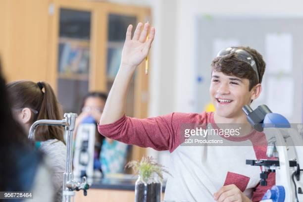 Cheerful teenage boy raises hand in chemistry class