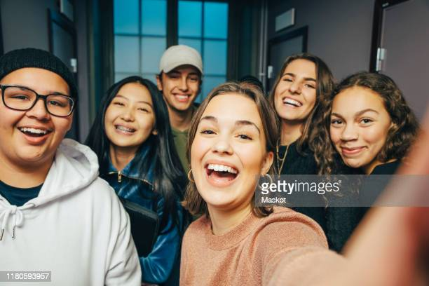 cheerful teenage classmates taking selfie in corridor - solo adolescenti foto e immagini stock