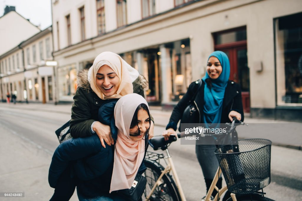 Cheerful teenage girl giving young woman piggyback by friend walking with bicycle on street in city : Stock Photo