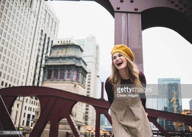 cheerful teenage girl standing on bridge against buildings in city - chicago illinois stock pictures, royalty-free photos & images