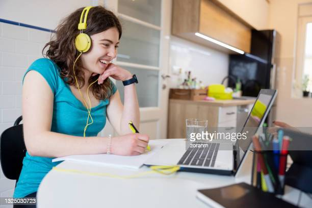 cheerful teenage girl with headphones on attending online class - 18 19 years stock pictures, royalty-free photos & images