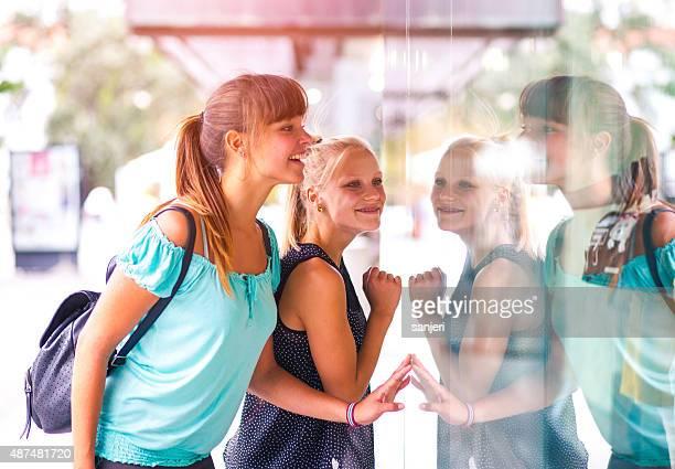 Cheerful teenage girls window shopping